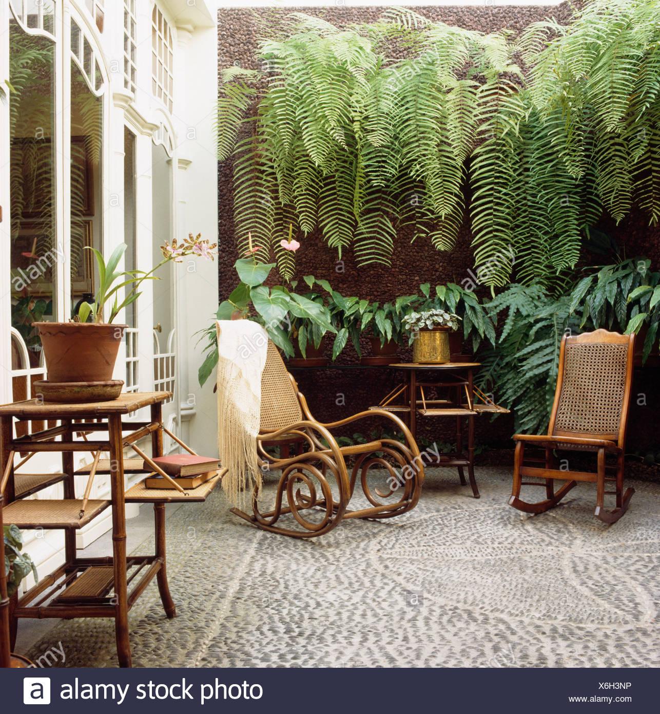 fougeres luxuriantes sur mur au dessus de meubles anciens en bois et rotin chaises bercantes sur petite cour avec pavage de mosaique de galets x6h3np