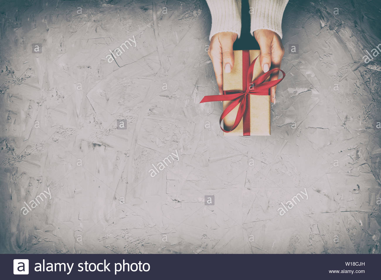 woman hands give wrapped valentine or other holiday handmade present in paper with red ribbon present box decoration of t on white cement table W18CJH
