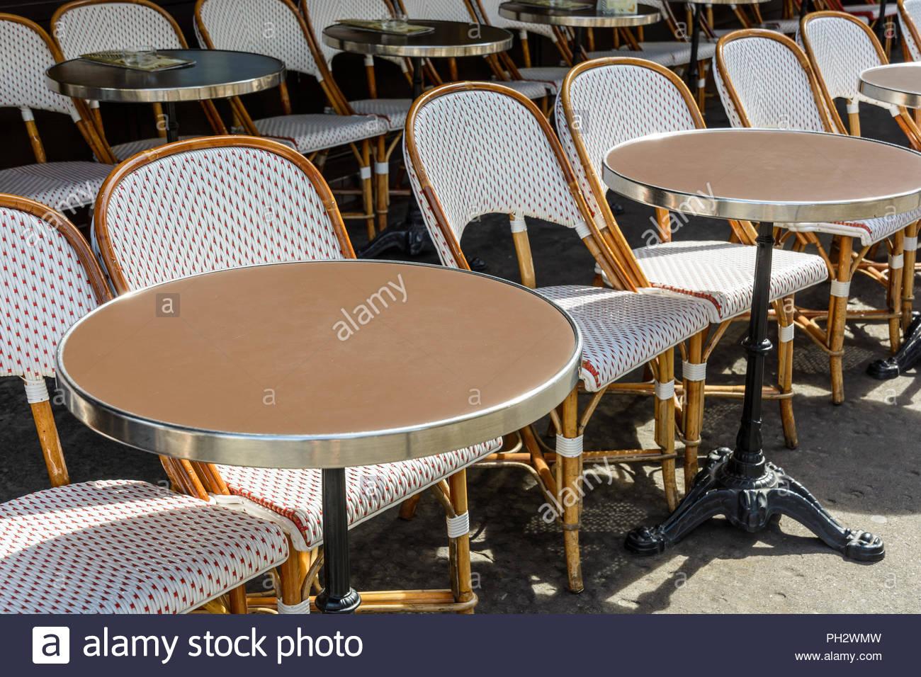 une terrasse typique a l exterieur d une brasserie parisienne mis en place avec des chaises en rotin et des petites tables rondes avec une jambe de fer de fonte ph2wmw