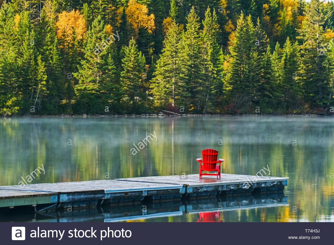 fauteuil muskoka sur dock a l automne feuillage couleur reflete dans l eau du lac tranquille de clear lake parc national du mont riding manitoba canada t74h3j