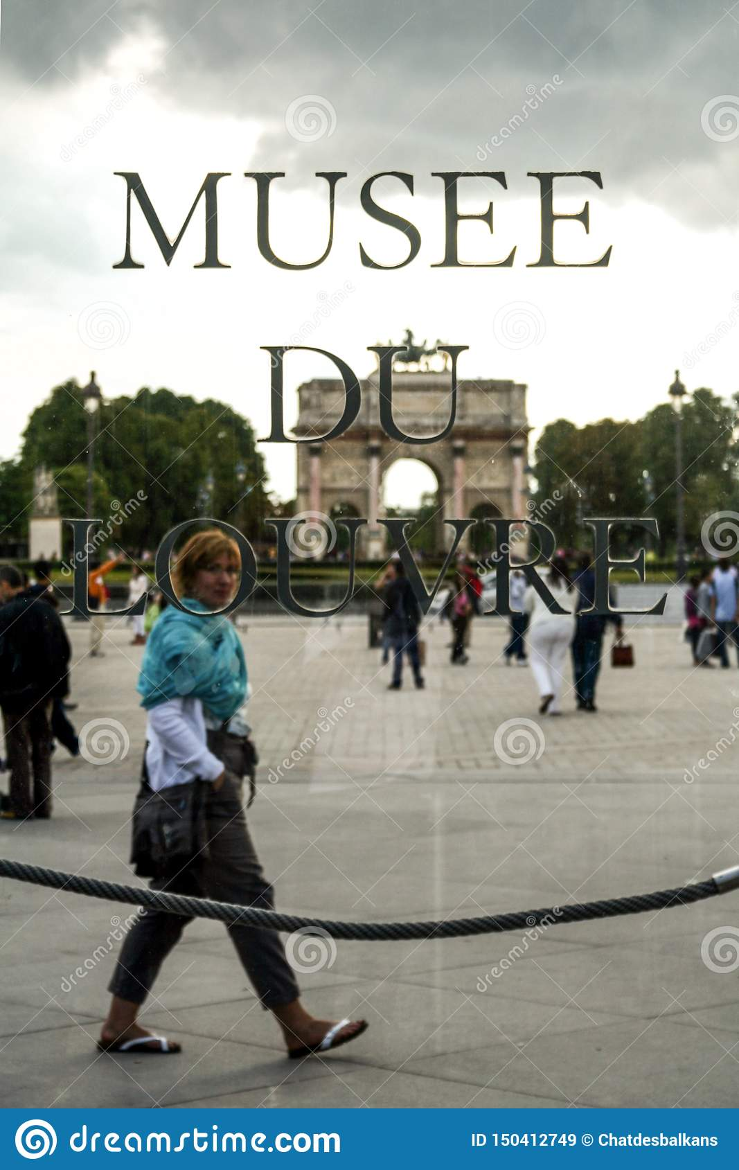 tourist passing behind logo louvre museum musee du louvre front jardin des tuileries garden paris france july