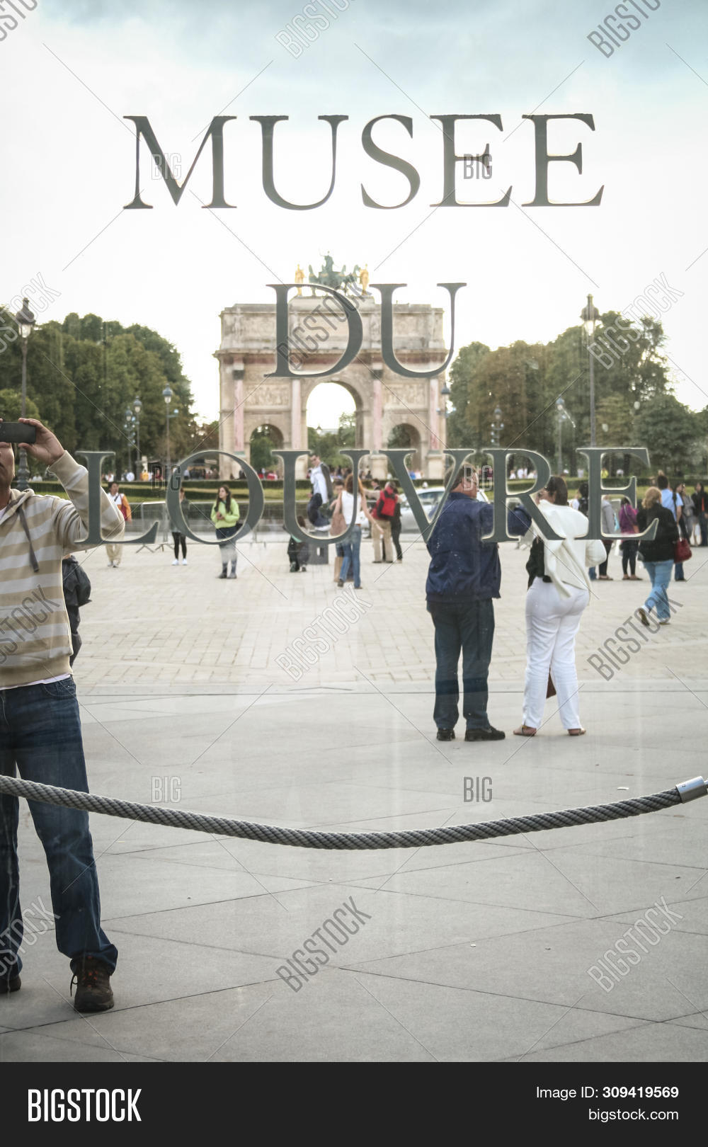 stock photo paris, france july 23, 2011: tourist taking pictures behind the logo of louvre museum (musee du lo